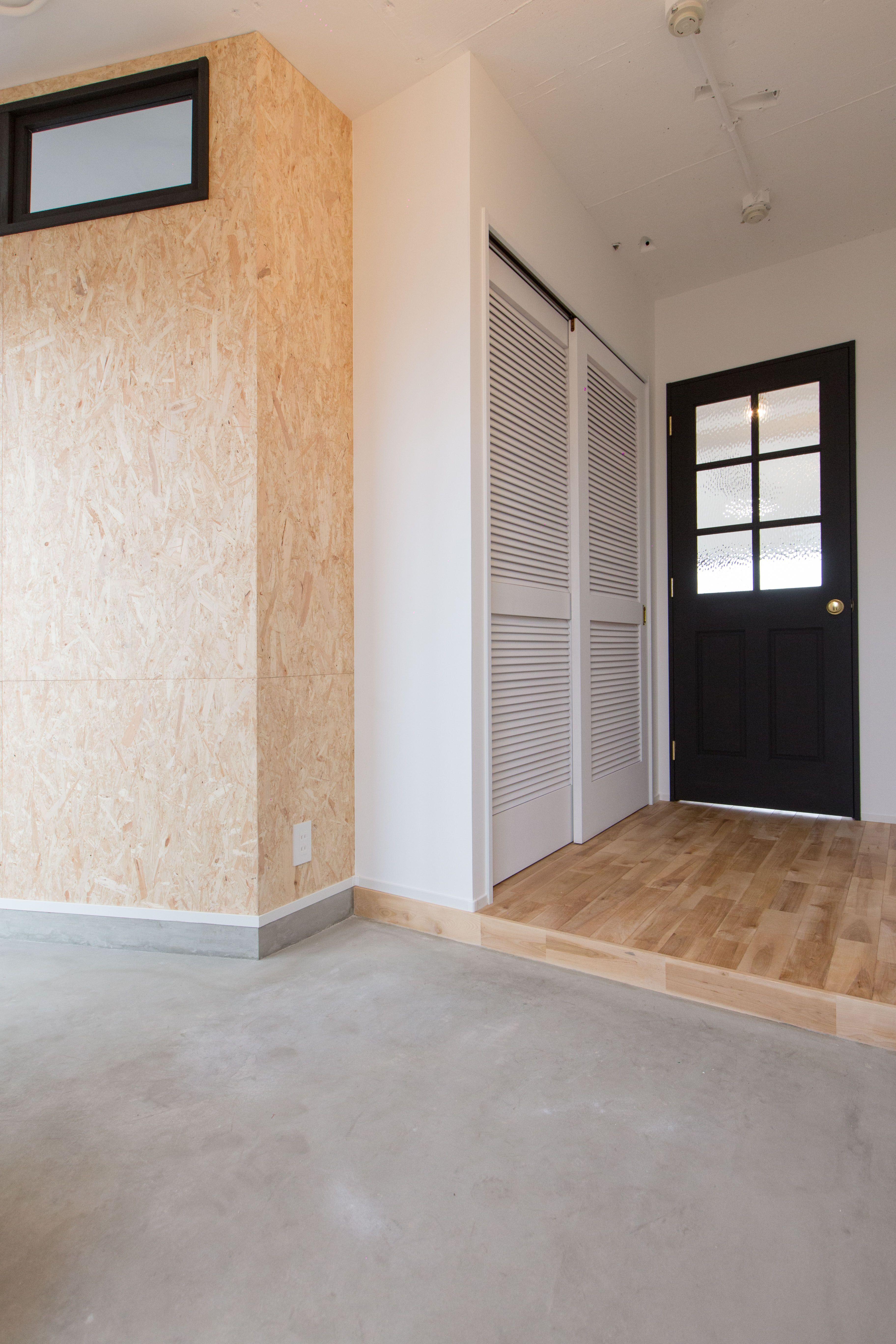 アメリカン風の玄関になっています 土間の色合いと黒い扉と室内窓が