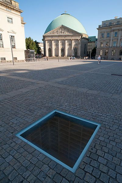 "Walking from the boulevard Unter den Linden to the Bebelplatz, you will probably see people who watch together on a spot on the floor. Only on closer inspection you can identify a sunken glass plate between the pavement that provides a view into a room full of empty bookshelves.The artist is Micha Ullman and is called ""Library"".The subterranean bookshelves could accommodate about 20,000 books: a reminder of the approximately 20,000 books, which the Nazis burnt on May 10th, 1933 on this place"