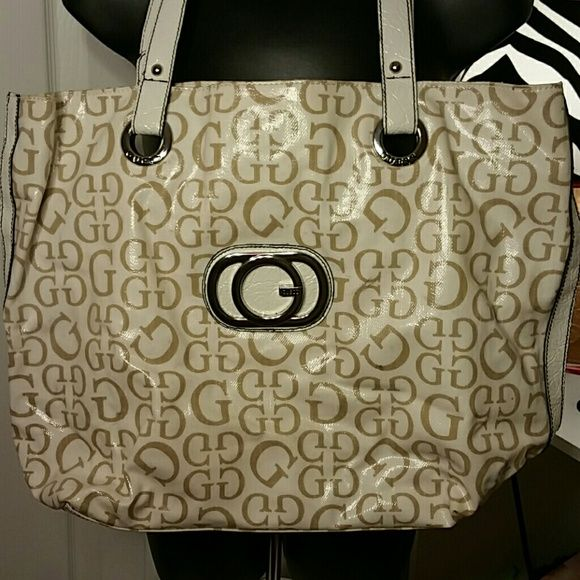 """Guess large tote bag Inside of this is super clean and has lots of pockets and one huge zipped compartment. Magnetic closure. Minor dark spots. See last pic. Measures about 19"""" long and 13.5"""" tall Guess Bags Totes"""