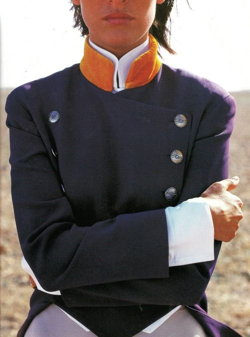 vintagebinger:  A beautifully cut coat of purple rayon with a saffron collar, paired with a matching blouse by Turkish-born designer Rifat Ozbek. Ozbek shot to fame in the late 80s and early 90s, showing his collections in London and Paris. Most recently, he started a new brand called Yastik by Rifat Ozbek, a line of limited edition cushions (yastik means cushion in Turkish). Photo from Mirabella, August 1992.