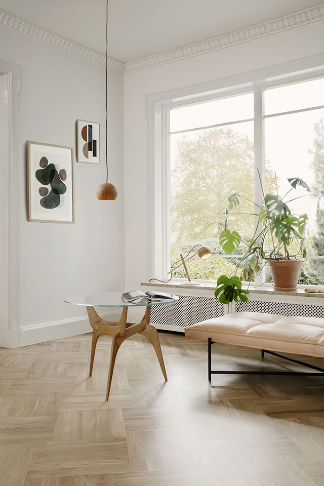 Der helle parkettboden großzügige weiße holzfenster und eine schlichte inneneinrichtung sorgen für ein stilvolles ambiente