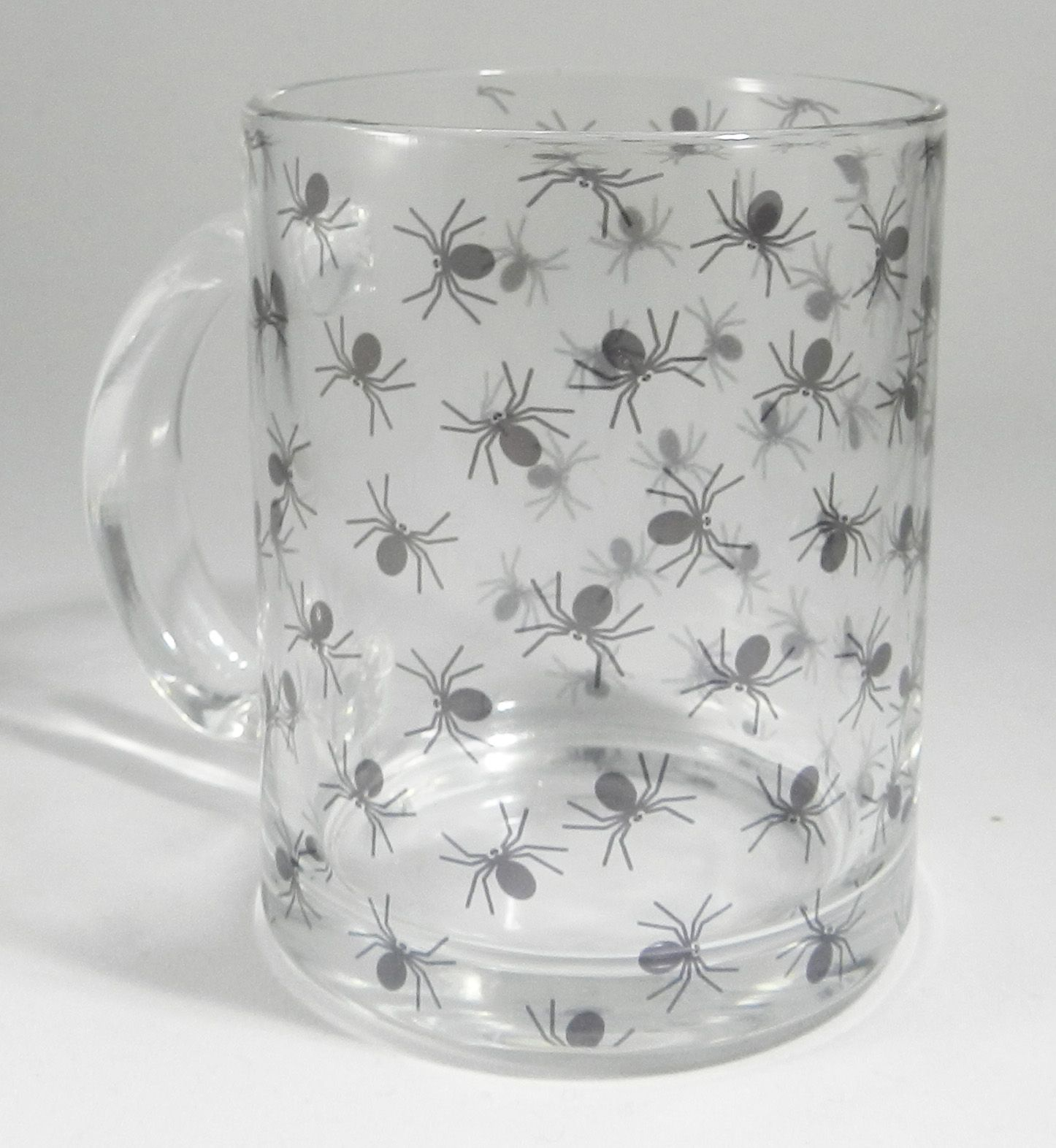 The Black Spider Glass Mug by Half a Donkey. Not for Arachnophobe's. A clear glass mug covered with black spiders. Vintage style mug with modern day design. Perfect for Halloween. High Quality Glass Mug which is dishwasher safe. Height 9.5 cm Diameter 8 cm Capacity is 315 ml (11oz) From the Series 9 Nature Range by Half a Donkey Ltd.