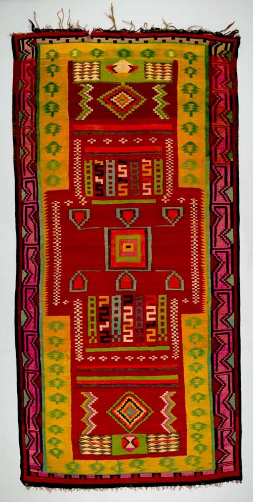 Africa   Floor rug from Gafsa, Tunisia   ca. 1930 - 70   Wool; interlocking tapestry woven   Kilims from Gafsa in central Tunisia are famous for their brightly coloured, bold geometric patterns arranged in panels and executed in the interlocking-tapestry weave. Though many motifs are repeated throughout a piece, they are never used in exactly the same colours or interpretation. Rows of marching camels (common beasts of burden in this area) are a signature of the Gafsa style.