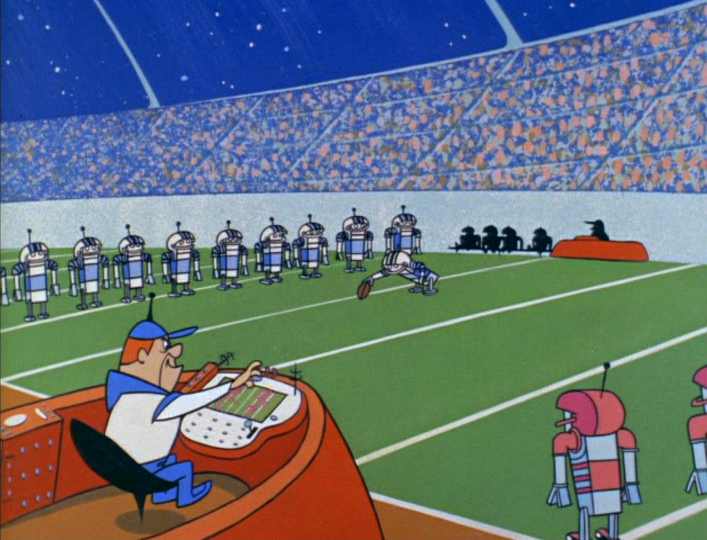 Jetsons Football: Coach controls all robot team at gaming console.