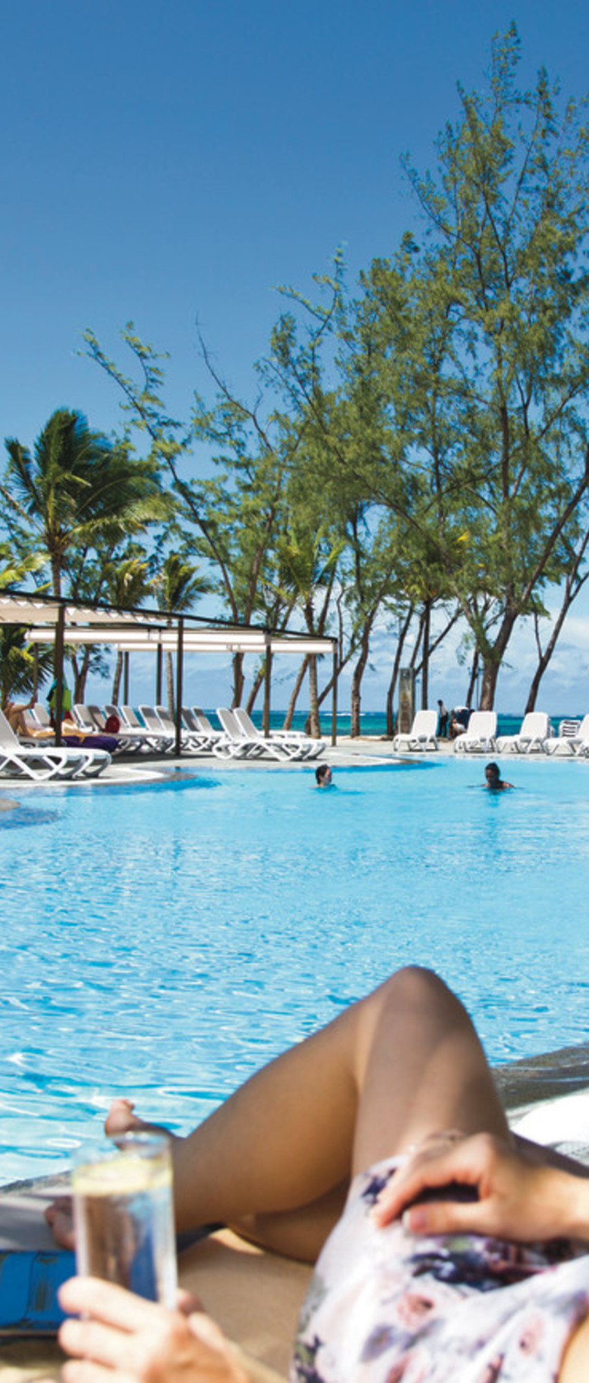 Relaxing by the pool with a cool drink and sea views in Mauritius ...
