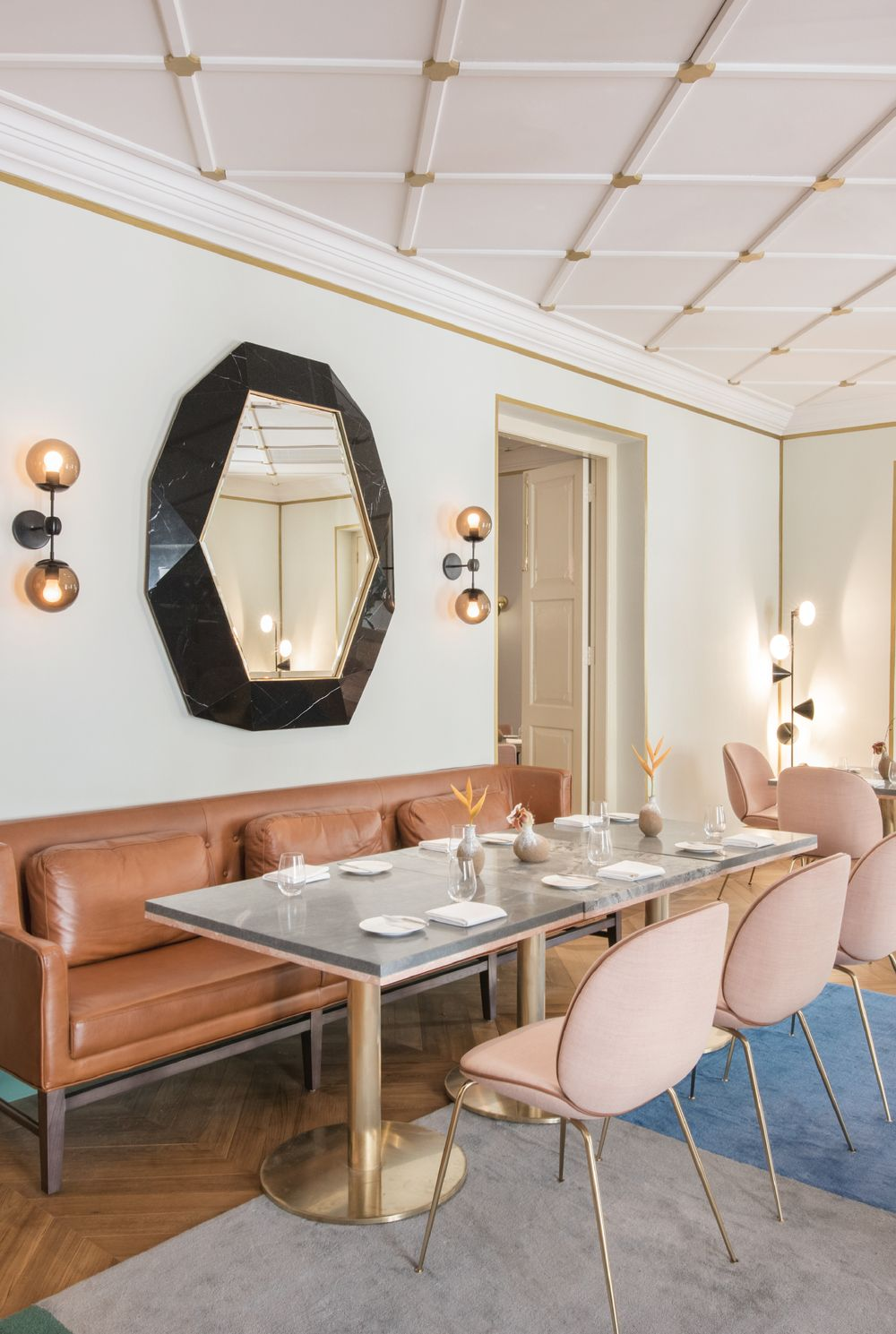 gorgeous dining room with blue carpet pink chairs and brown leather banquette