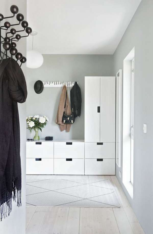 Cabinets and plenty of hooks keep this Nordic minimalist entryway organized.