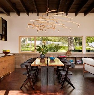 Hog Pen Creek Residence - contemporary - Dining Room - Austin - Lake Flato Architects The steel-base dining table, which separates the living room and kitchen, is topped with a slab of pecan from the property's felled tree.   Chairs: Tom Dixon; light fixture: Ingo Maurer