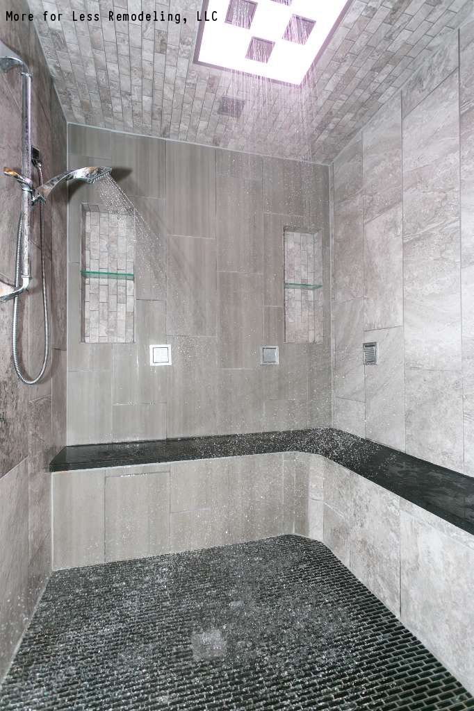 A Modern Walk In Shower With A Large Shower Bench And Black Tile