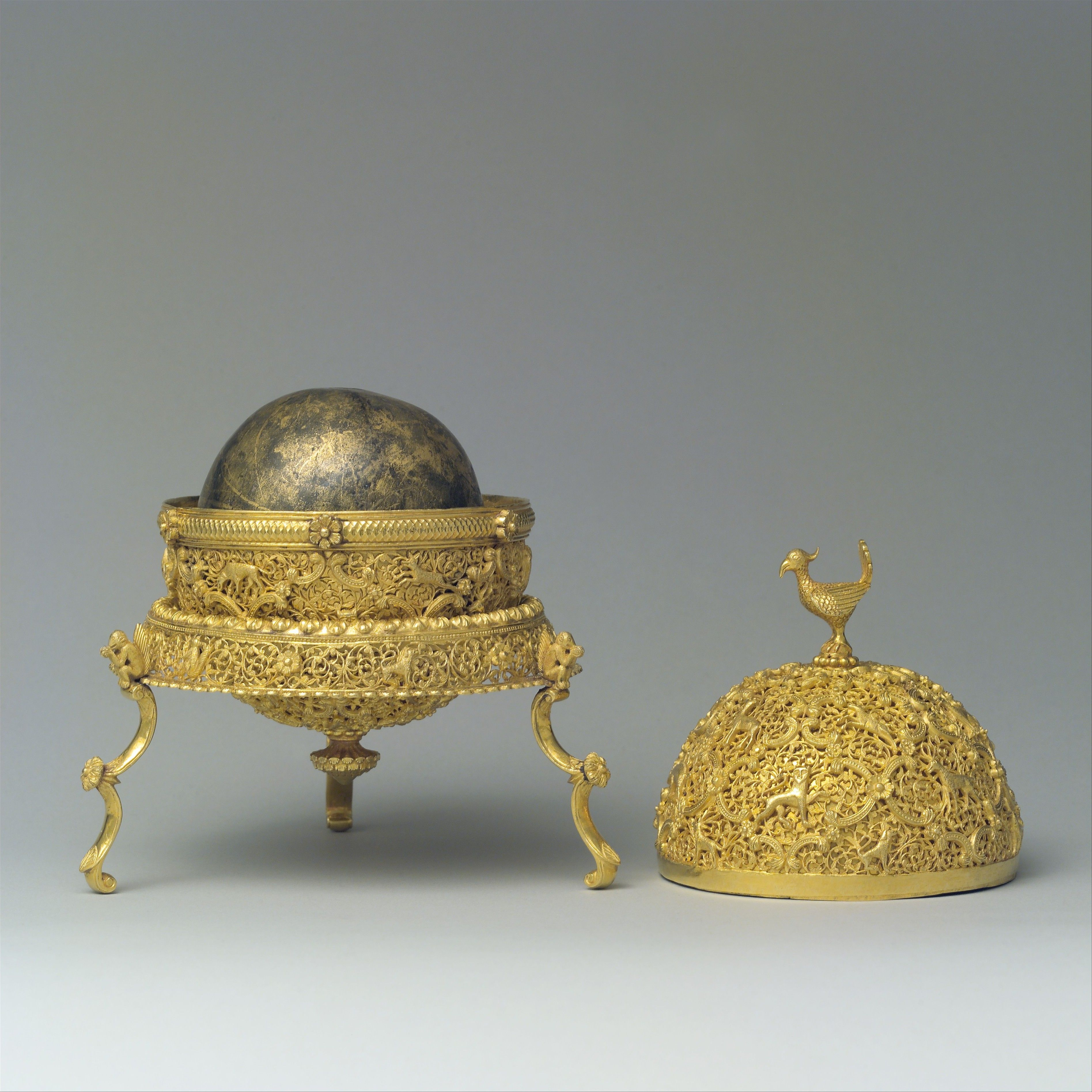 Goa Stone and Gold Case. Object Name: Goa stone and container. Date: late 17th–early 18th century. Geography: India, Goa. Medium: Container: gold; pierced, repoussé, with cast legs and finials Goa stone: compound of organic and inorganic materials.