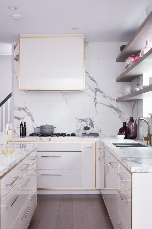 White And Gold Kitchen Features White Lacquered Cabinets With Gold Trim Paired With Gray And White