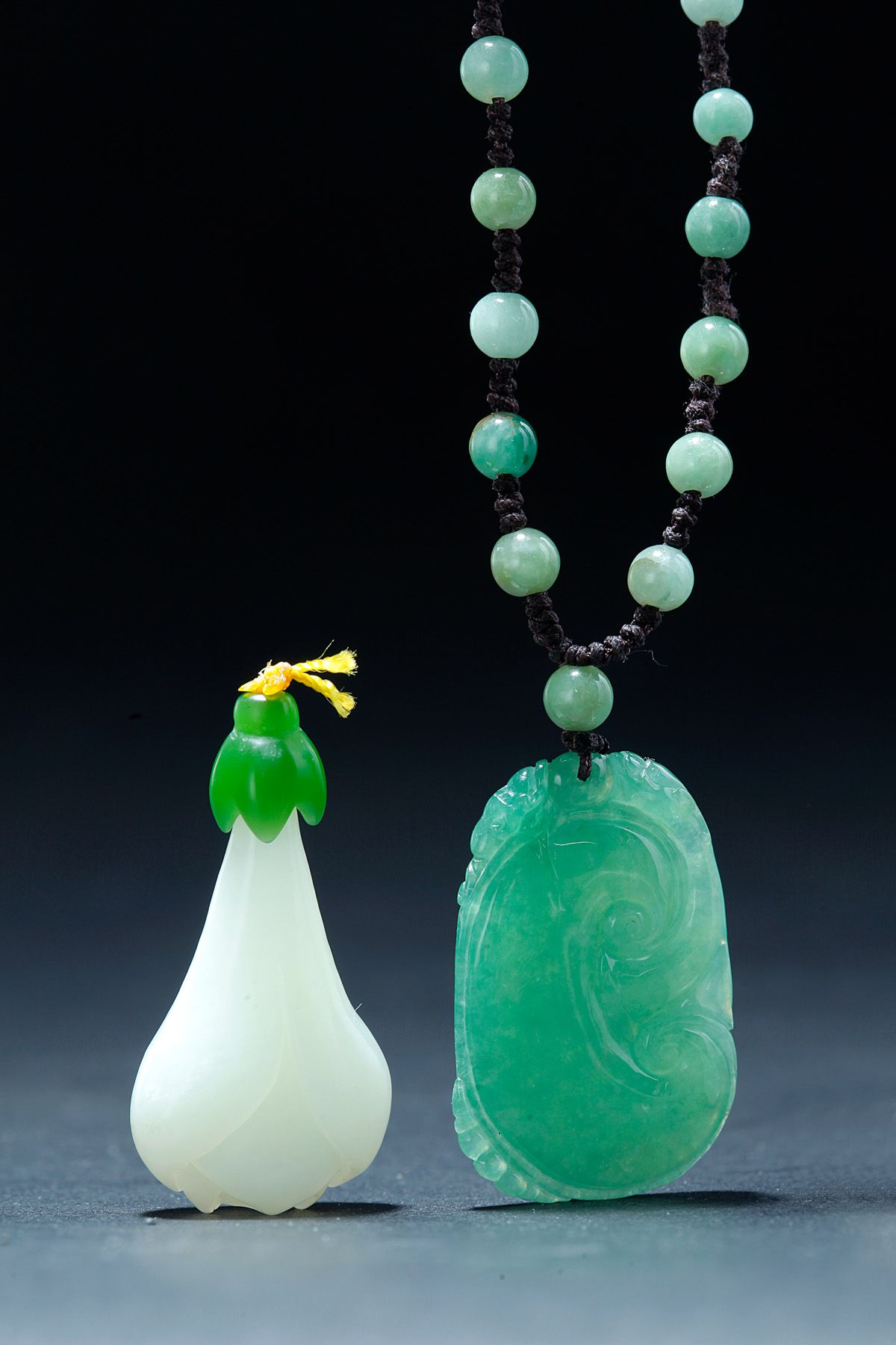 """TWO CHINESE JADE AND JADEITE PENDANTS.  Nineteenth-20th century. Green ice jadeite and white jade. Necklace with small beads and a carved LinZhi ( RuYi) pendant, 1.5""""h. and a finely carved white magnolia. 1.5""""h.  Estimate $ 2,000-3,000 garths.com"""