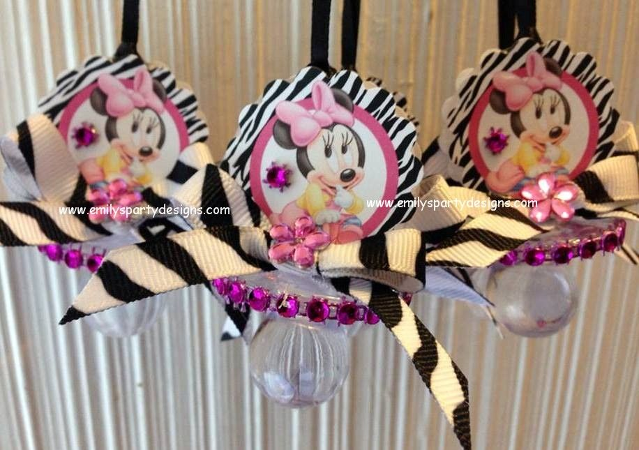 """This beautiful Baby Minnie Mouse pacifier necklace are a fancy way to present favors for your Baby Shower. Use these cute baby shower pacifiers as baby shower favors and a """"Don't Say Baby"""" game. The necklace is made of 1/8 satin ribbon. Each pacifier measures 2 1/2"""" long. Have two-sided Minnie Mouse and bows."""