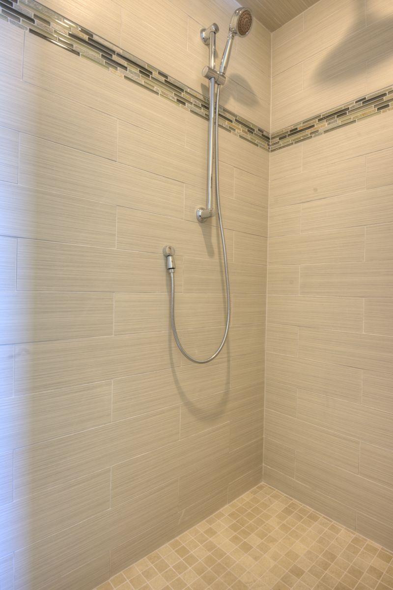 walk in tile shower, no door. Double shower heads, handheld and ...