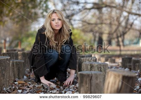 A outdoor portrait of a beautiful long-haired blond young woman, posing in a park in late fall. Shallow depth of field. by area381, via ShutterStock