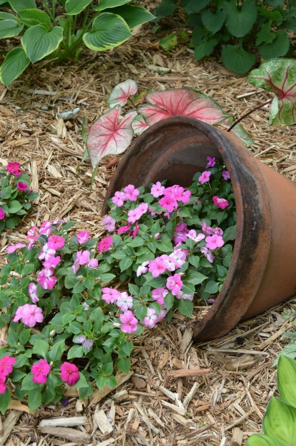 I think whimsical garden art really makes a backyard flower bed.  I love these 20 diy ideas that are either recylcled, upcylcled, or from junk that nobody wants.  I need to do some of these in my outdoor space--what a neat way to use a broken pot. #gardenart #whimsical #flowergarden #landscapingideas