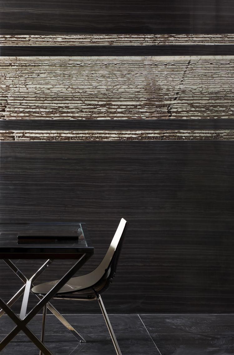 This wall by Lapicida is clad in a slab featuring three stripes of Liquorice marble contrasted with Imperial Black marble - both marbles have been vein cut; sawn vertically down through the stone bed to reveal millions of years of natural stratification. www.lapicida.com