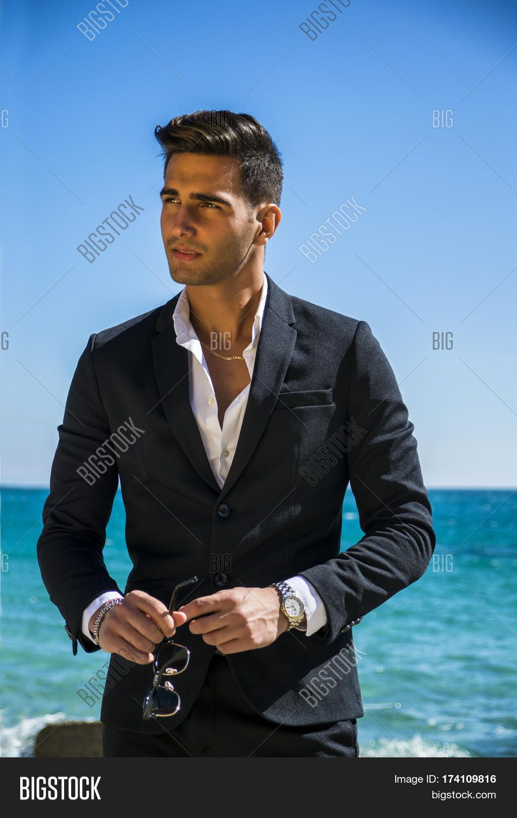 3be91afdbed Young handsome man in elegant white shirt and business suit, on beach while  looking away. Sea waves on background