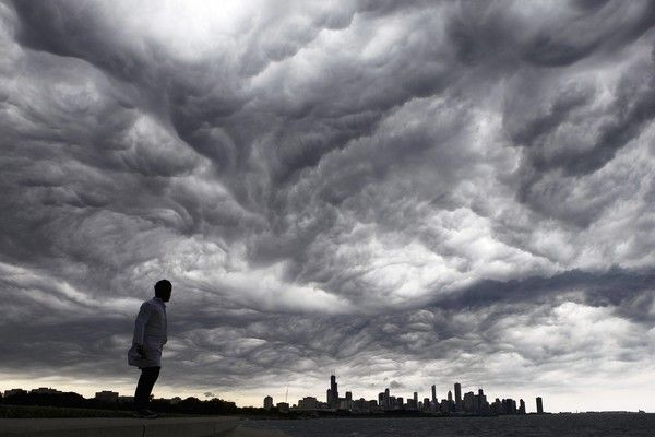 ( Alex Garcia, Chicago Tribune / July 1, 2011 ) Dev Patel, of Chicago, looks toward the cloud-shrouded Chicago skyline from the South Side lakefront. The cloud cover, caused by what's known as an outflow boundary, kept temperatures much lower than predicted.