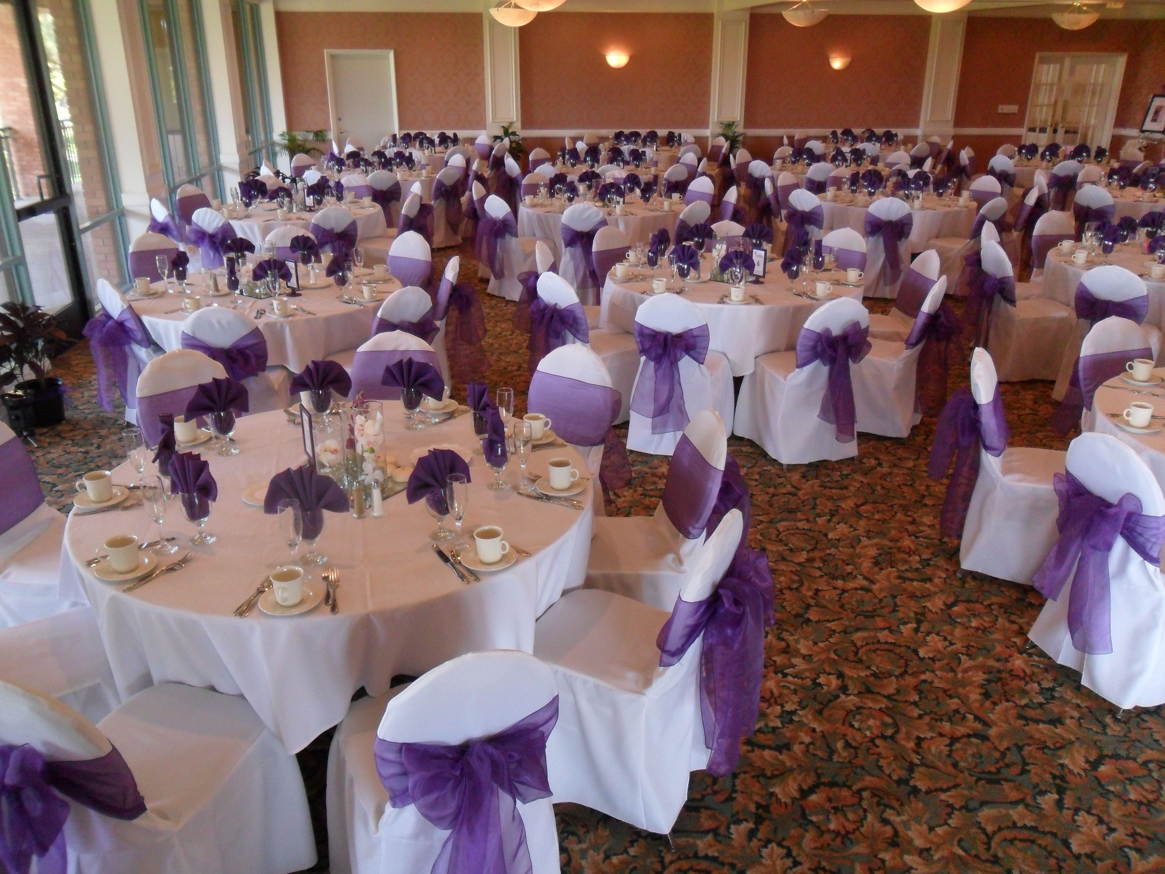 Regal Purple Bows On White Chair Covers Available For Rent