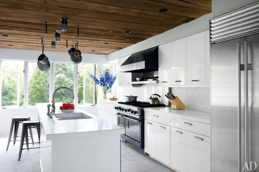 A Viking range and hood were chosen for the kitchen of director Shaw Levy's Hudson Valley retreat; the lights are vintage marine fixtures, the backsplash is of honed marble, and the sink fittings are by Waterworks.
