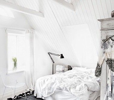 Une chambre sous combles avec un plafond en lambris blanc ...