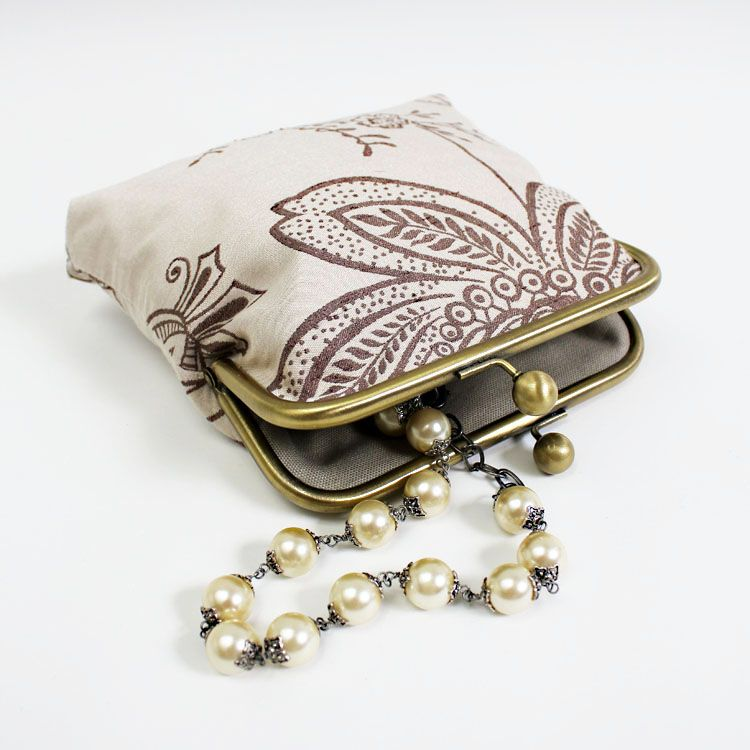 Lovely soft romantic cosmetic or jewellery pouch in oatmeal brocade fabric with a floral design The kisslock frame is brass
