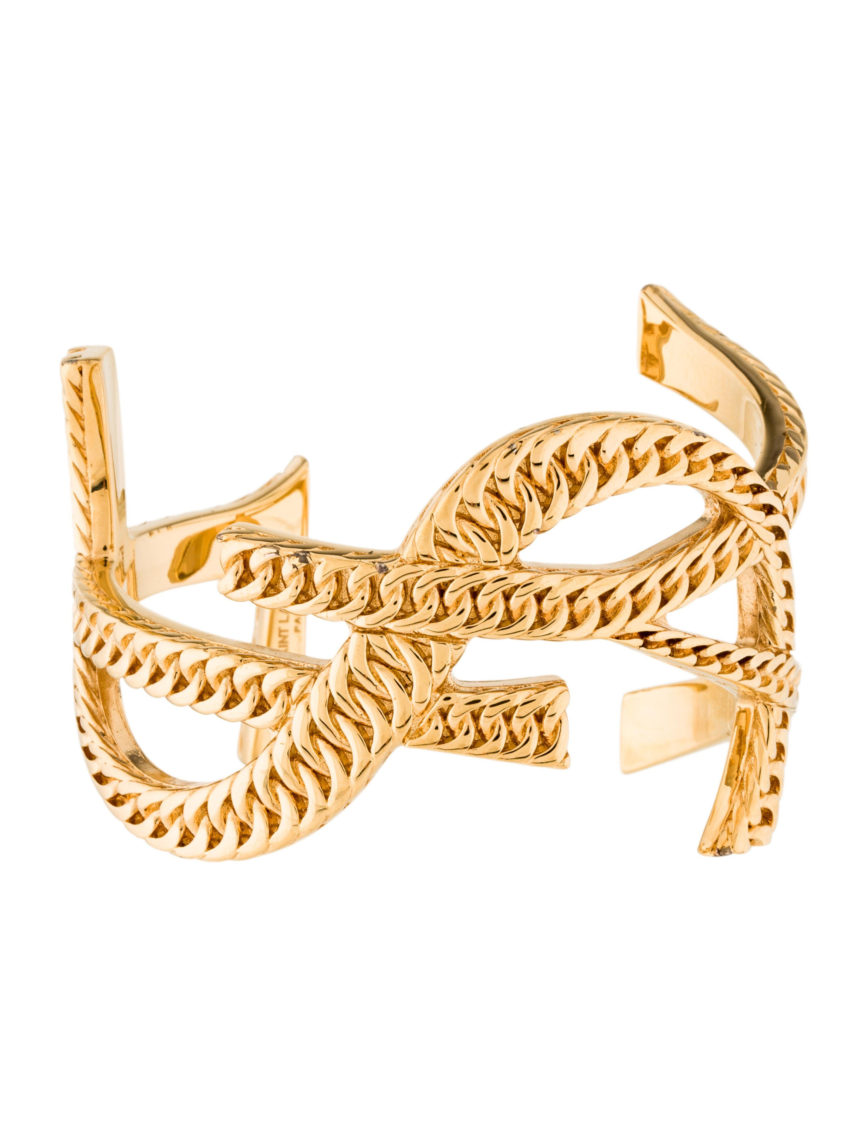 78ff26b58ac3 Gold-tone Yves Saint Laurent Monogram Cassandre cuff bracelet featuring  textured brand logo and high polish finish throughout.