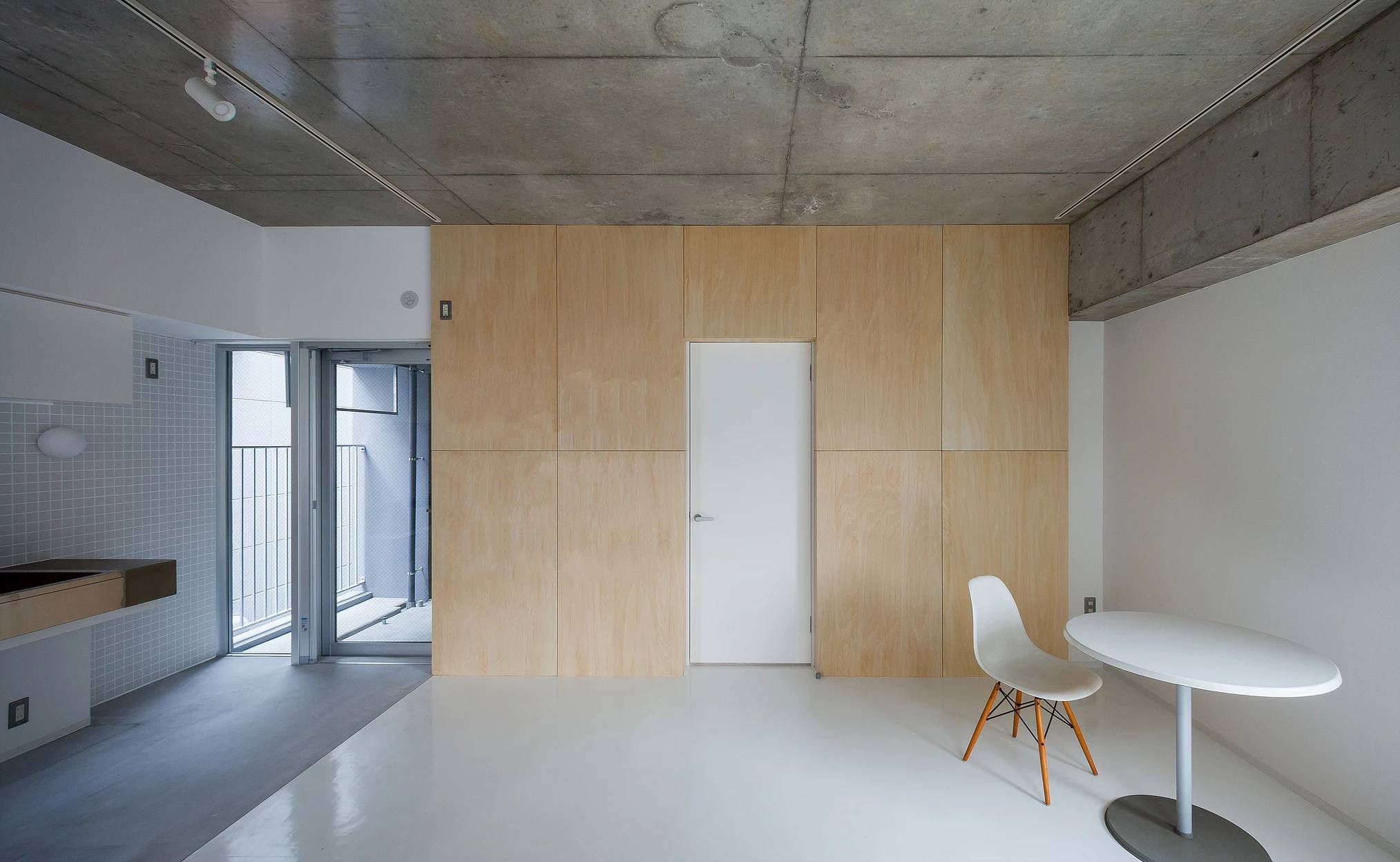 Kudo is a minimalist multi-residence located in Nagoya, Japan, designed by WORKCUBE. Although the space is small, an internal courtyard allows for additional natural light to enter the space without compromise to privacy. The complex has a garage specifically for bicycles, and utilizes a camera-equipped intercom. The entrance is outfitted with two large Douglas Fir doors. The floors are epoxy white for easy cleaning, and maintains a minimalist aesthetic.
