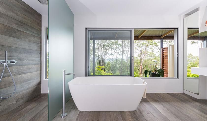 This Byron Bay bathroom has been designed as one free-flowing open space. The freestanding bath is a statement amongst the expansive windows and luxurious mirror. #openspaces