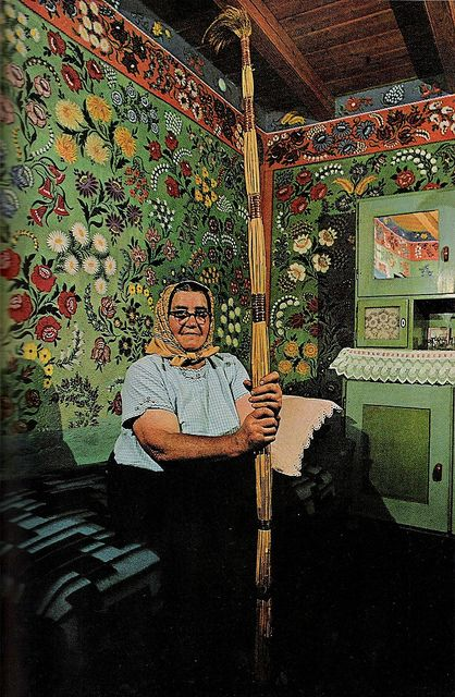 """April 1971 -   """"A whole house for a canvas: Mrs. Lajosne Vargacz sits before a bedroom mural painted with the help of her neighbors at Kalocsa. Such folk art, once common in the region, today has few practitioners. Cane-and-feather duster resembles the long-handled paint brushes the artists used to decorate hard-to-reach heights."""" Via Sara Gossett"""