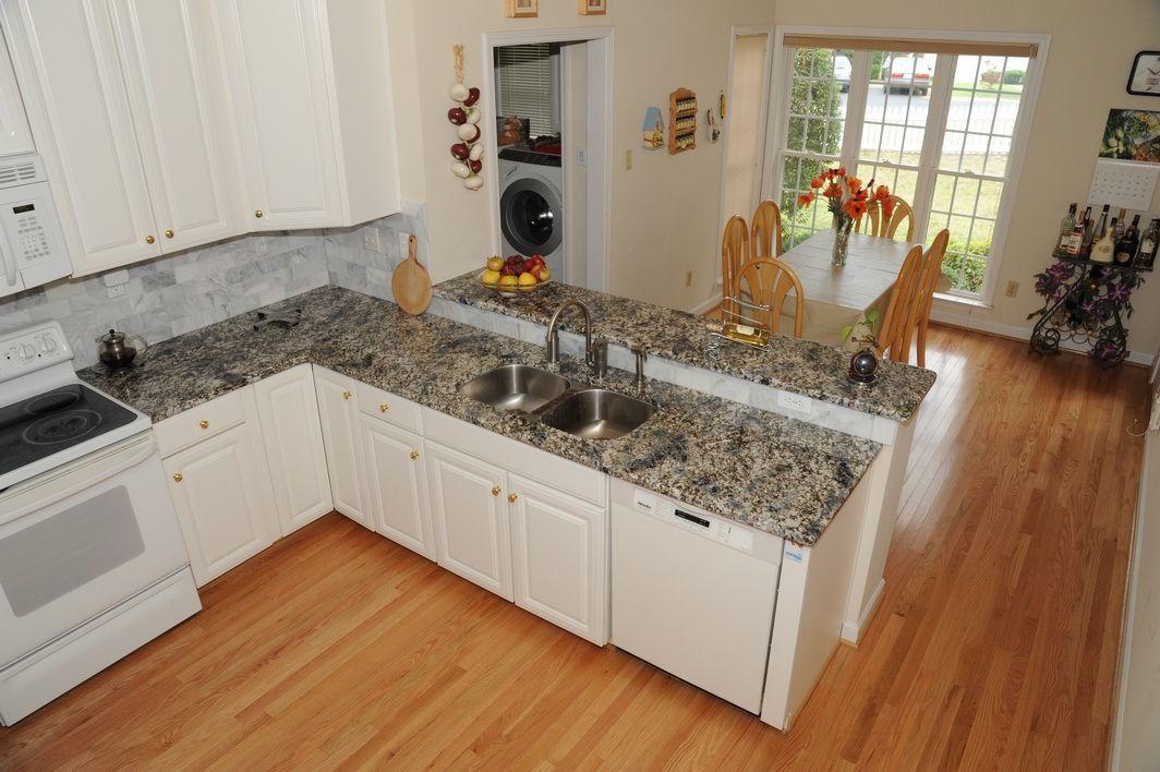 White kitchen with Azul Aran granite countertops ...