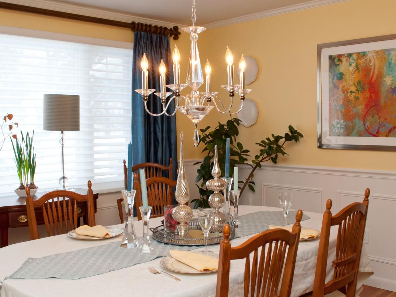A Low Hanging Crystal Chandelier Hangs Above A Dining Room Table, Covered  In A