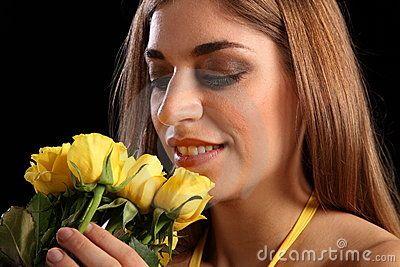 Mujer tiene en sus manos unas rosas amarillas.