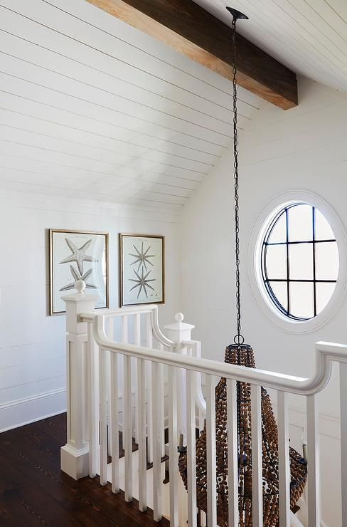 A brown beaded chandelier hangs over a white staircase from a shiplap vaulted ceiling accented with a rustic wood beam, while starfish art is mounted to a shiplap wall adjacent to an oval window. #vaultedceilingdecor