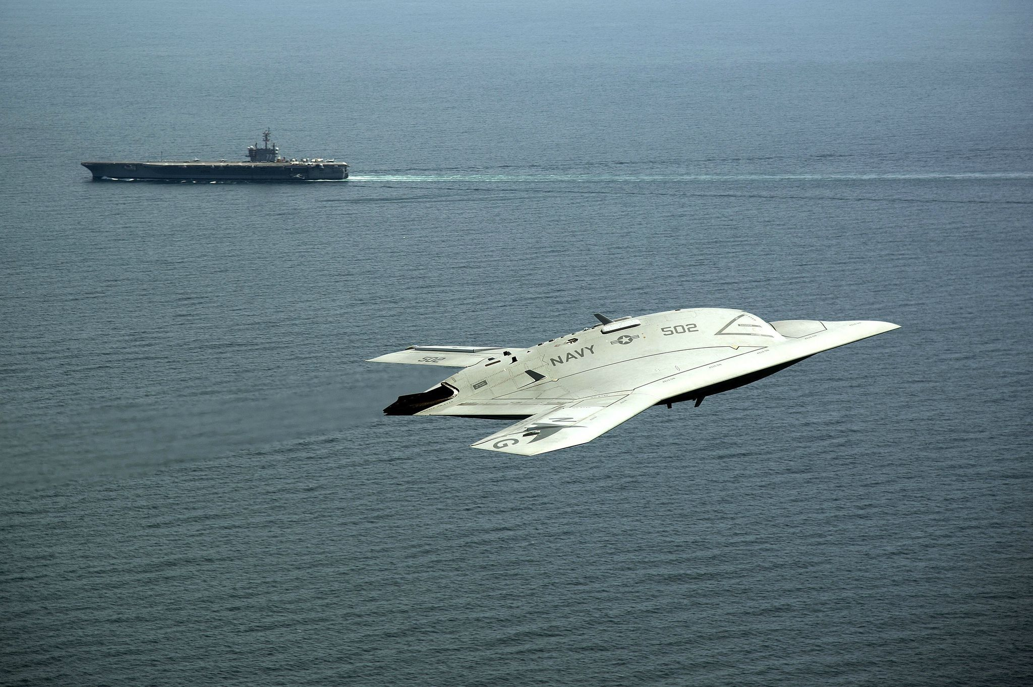 An X-47B UCAS malcontent flies nearby USS George H.W. Bush.