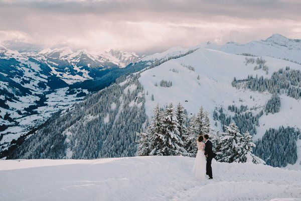 Lines of evergreens, jutting mountains, and steep slopes — we can't blame this couple for gazing at this winter wonderland.