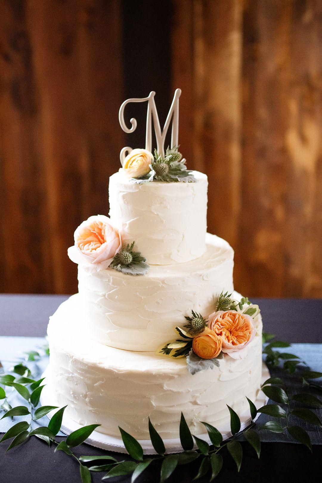 An elegant white wedding cake with soft orange and green