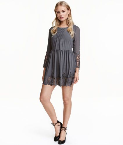 Dunkelgrau. Kurzes Chiffonkleid mit 3/4-langen Trompetenärmeln. Das Kleid hat Biesenfalten oben und Spitze an Ärmelenden und Saum. Cut-out im Rücken mit