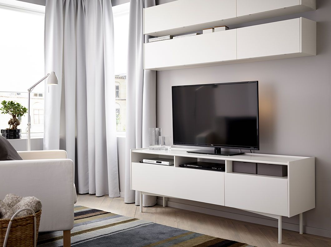 A living room with wall cabinets and a TV bench, all in white ...