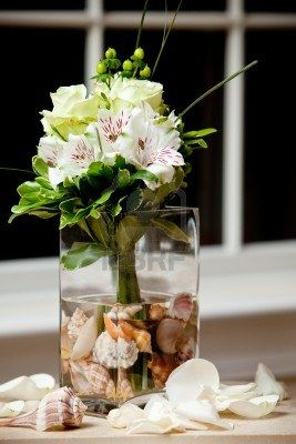 a wedding bouquet in a vase filled with water and sea shells Stock Photo