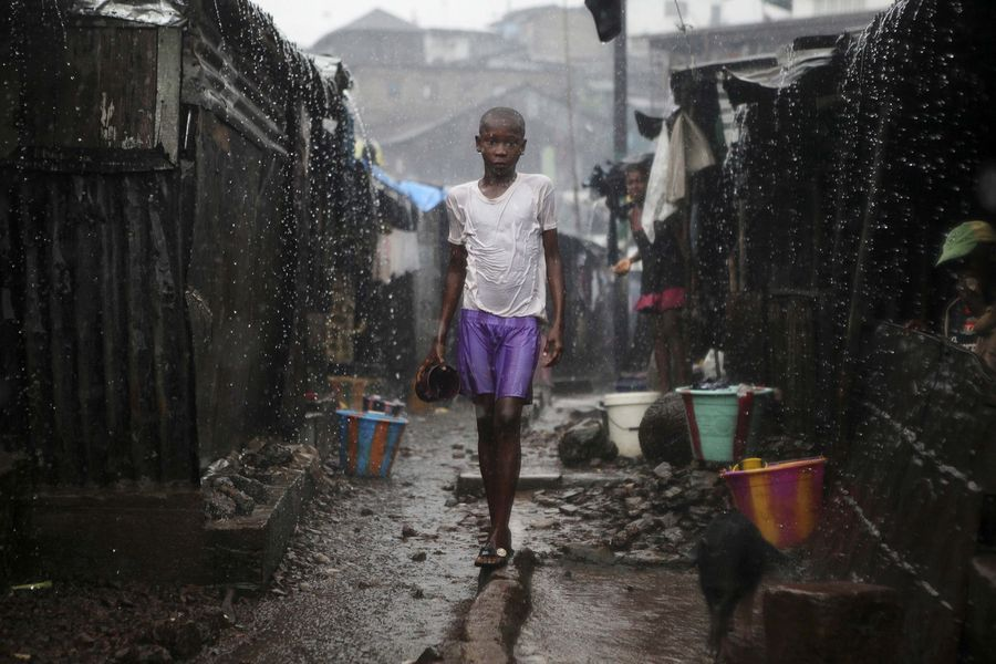 A child stands in the pouring rain in the slum of Susan's Bay in Sierra Leone's capital Freetown. (Reuters)