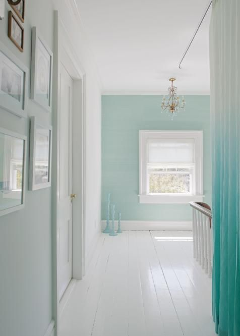 White painted wood floors and pale blue walls transform this hallway into a light, airy space, like stepping into clouds.