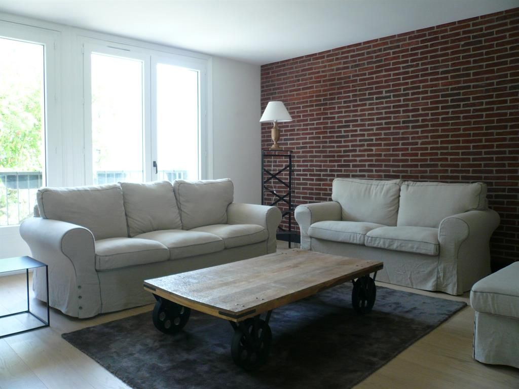 Living Room With A Brick Wall And An Original Coffee Table In Domozoom