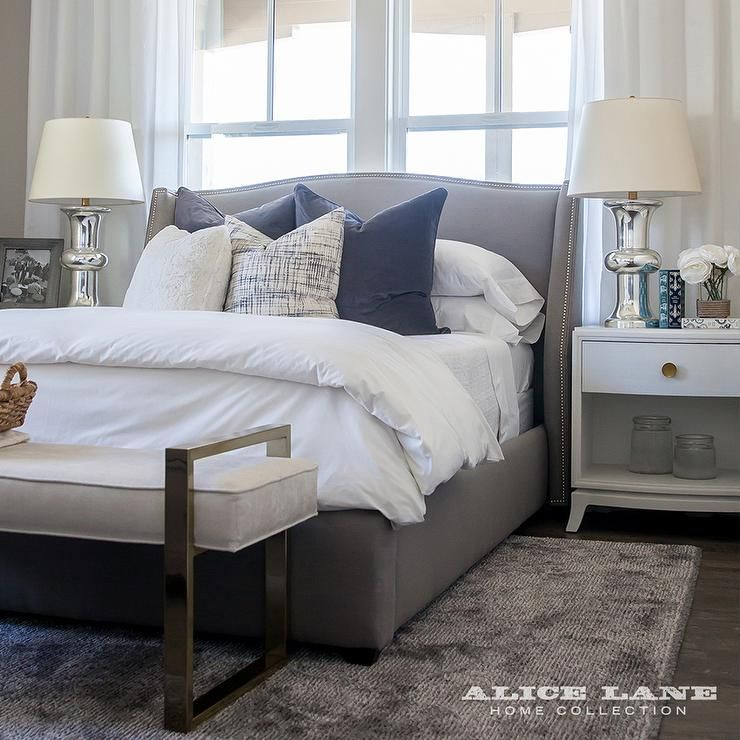 Contemporary bedroom features a charcoal gray wingback bed dressed ...