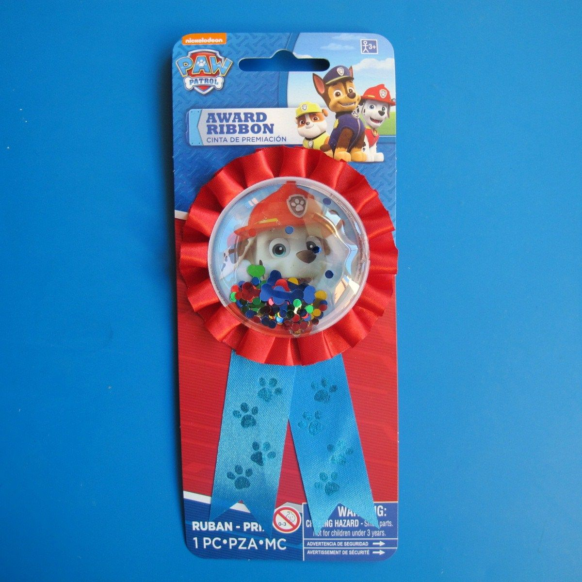 A Paw Patrol rosette, with a picture of Marshall and glitter shapes including bones which bounce around freely within the main picture. £2 each  https://littlepartyparcels.co.uk/shop/paw-patrol-rosette/