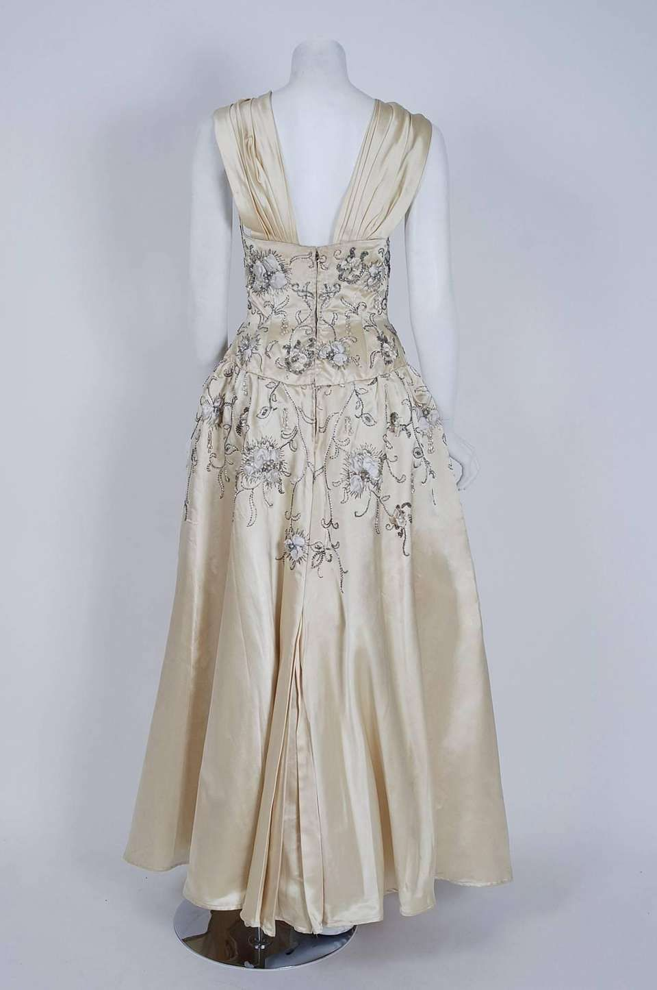 0d6701b8 For Sale on 1stdibs - Breathtaking mid-1950's ivory white satin ballgown  attributed to Pierre Balmain. This iconic designer created a very  sculptural ...