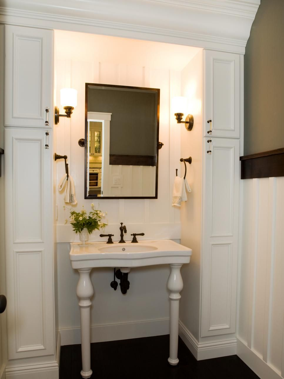 A stylish white pedestal bathroom sink is nestled inside crisp white cabinetry, accented with elegant fixtures.