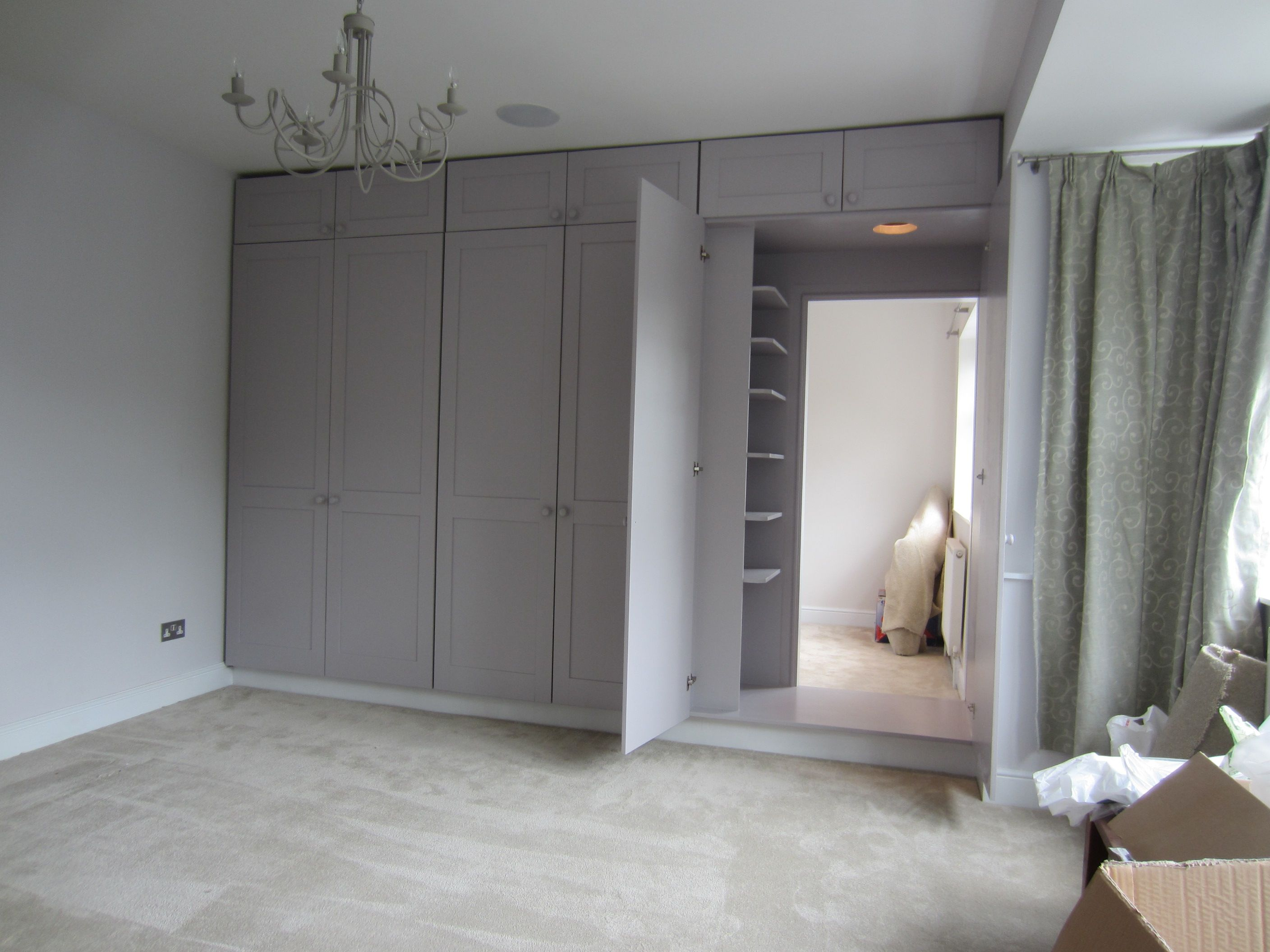 Wardrobe doors reveal hidden dressing room containing additional wardrobe units image 2 of 3 Master bedroom ensuite and wardrobe
