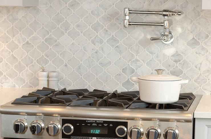 A Stainless Steel Stove Is Mounted Against Gray Marble Arabesque